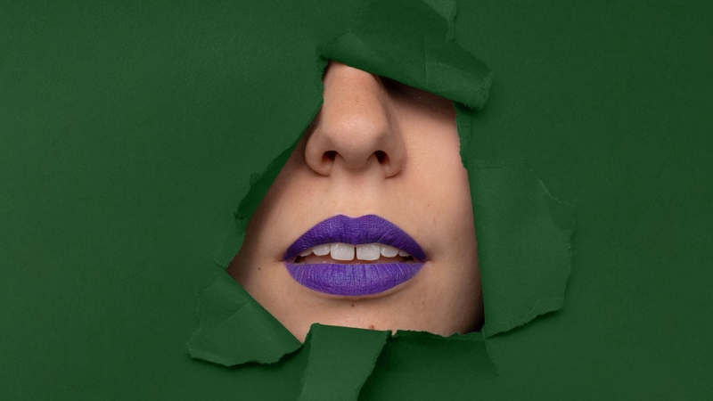 Image of purple lips with green background