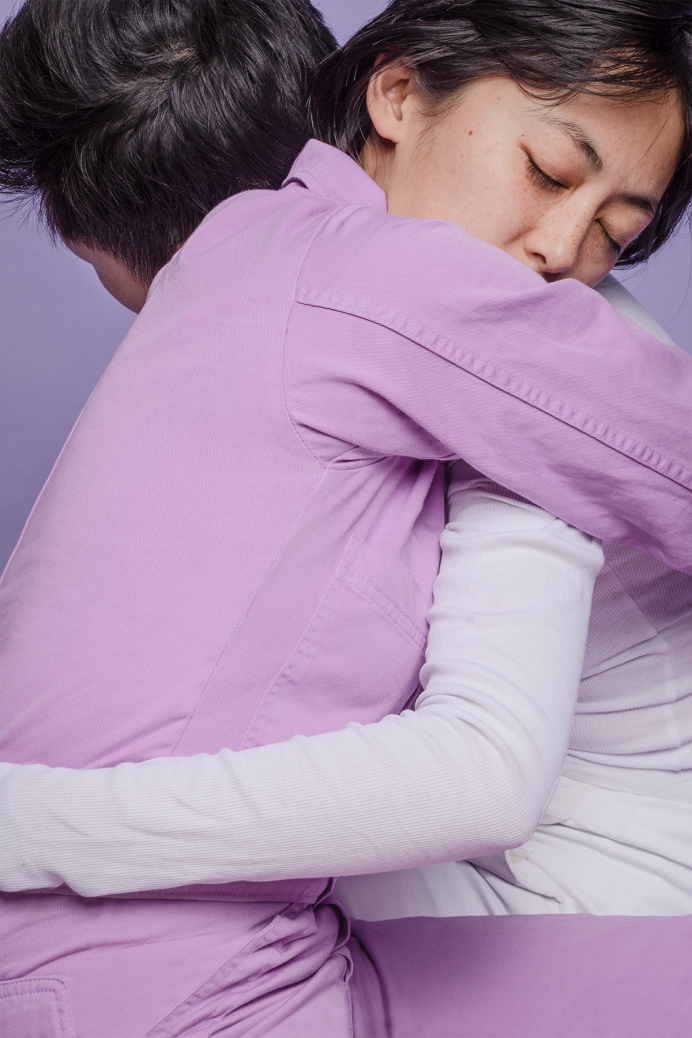 Two people hugging wearing purple and white clothes