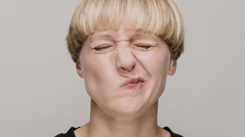 Person with eyes closed scrunching up nose