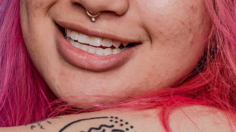 Woman with pink hair smiling. Bottom half of face