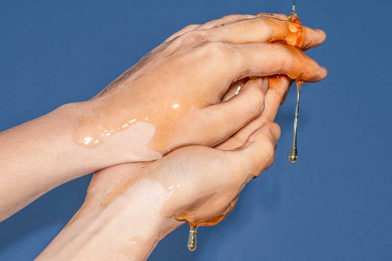 Closeup of hands with golden liquid over them
