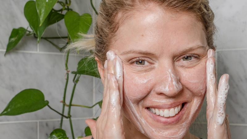 Woman smiling and applying cleanser to face in front of a plant and gray tile background