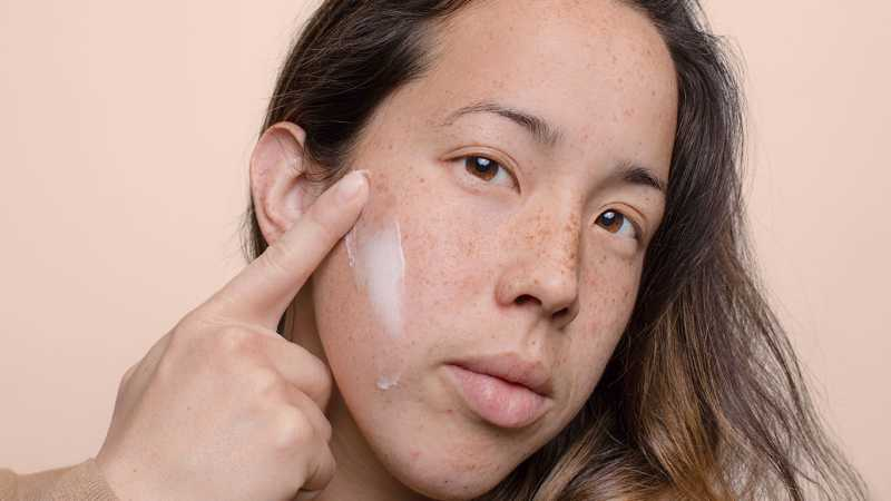 Closeup of woman's face and hand applying cream (large image version)