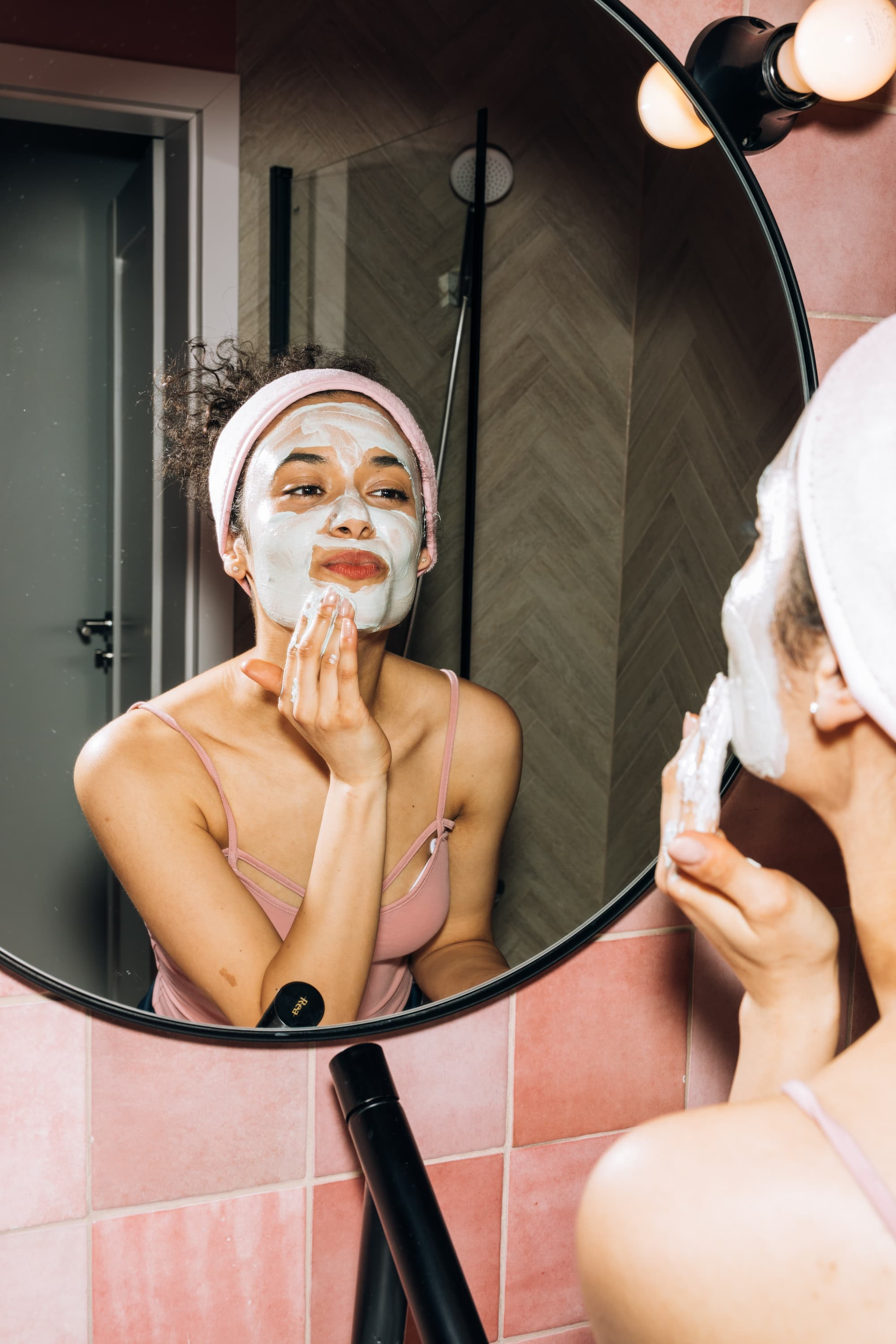 Woman looking in mirror with cream face mask