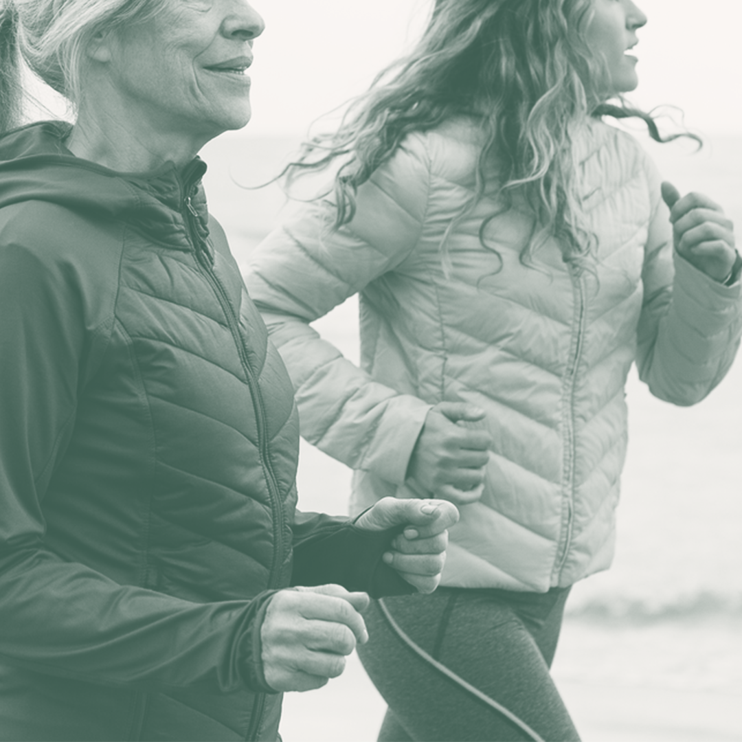 An image of two women running together on the beach.