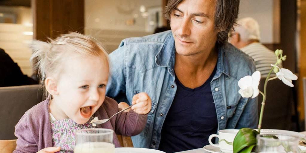 Ojciec patrzy na córkę podczas gdy ona je obiad