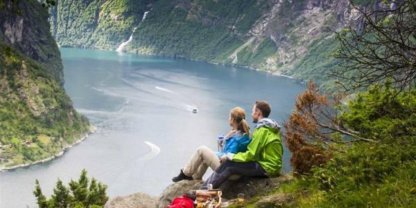 Paar sitzt auf dem Stein in Geirangerfjord in Norwegen