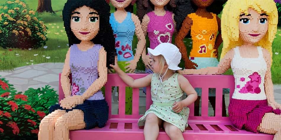 A toddler sitting on a bench with a group of giant Lego figures of other girls.