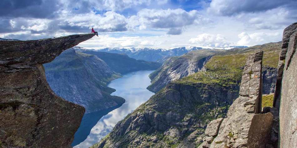 Person sitting on a rock overlooking Norwegian Fjords