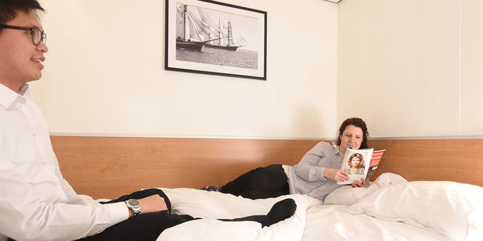 Two friends relaxing and reading magazines on the bed in a double bed cabin