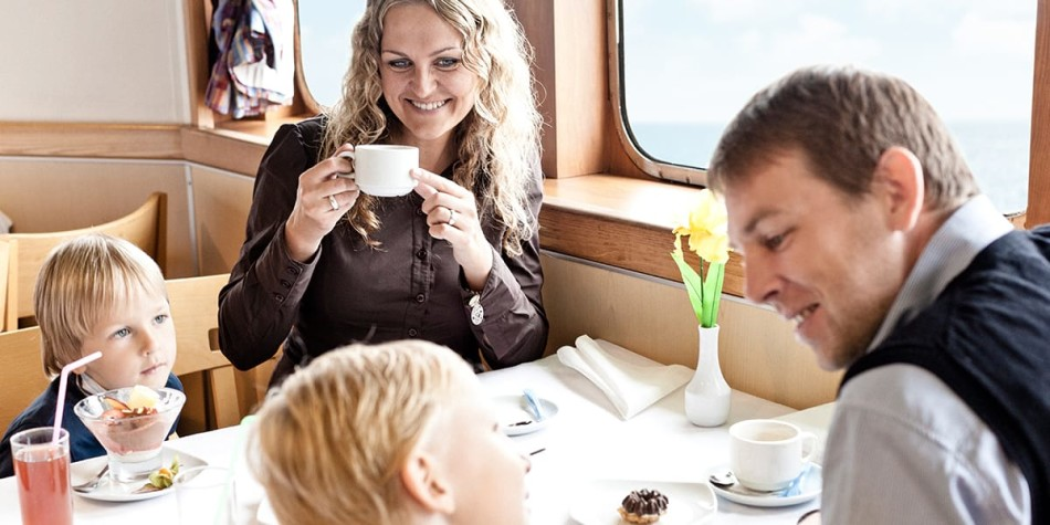 Family of 4 enjoying their meal at restaurant onboard Athena Seaways in the Baltics