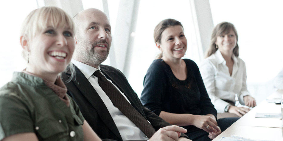 Four people smiling together at a meeting
