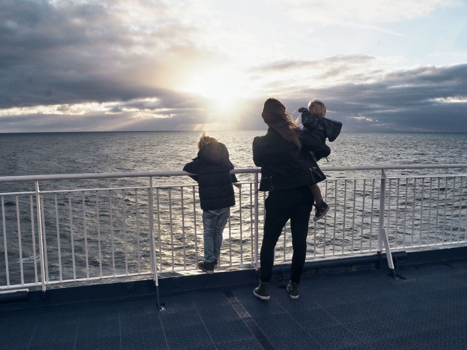 A woman and two children looking at the horizon on board a DFDS freight shipping vessel