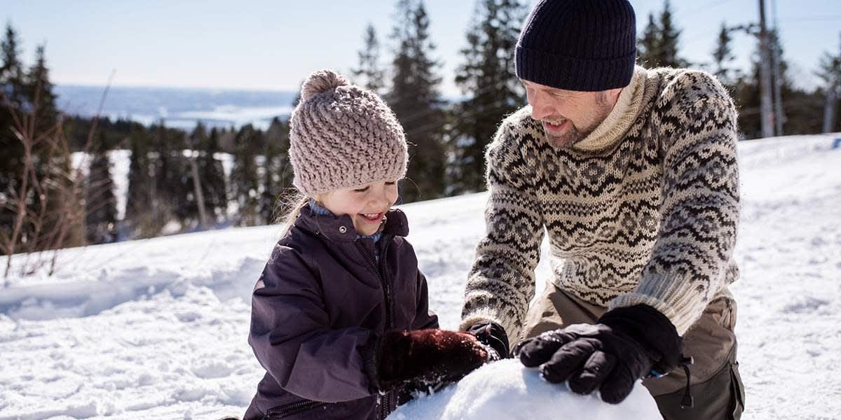 Far og datter bygger en snemand