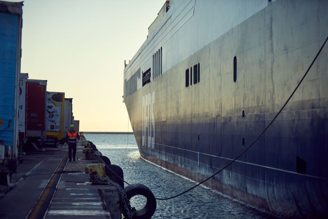 An employee walks along a DFDS ship docked at Trieste