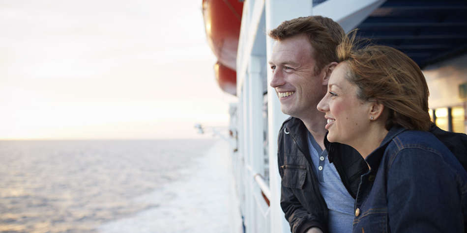 Couple smiling on deck during a ferry crossing