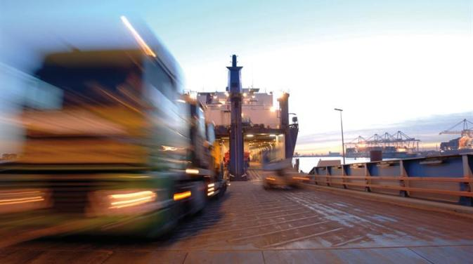 A truck in motion unloading from a DFDS ship