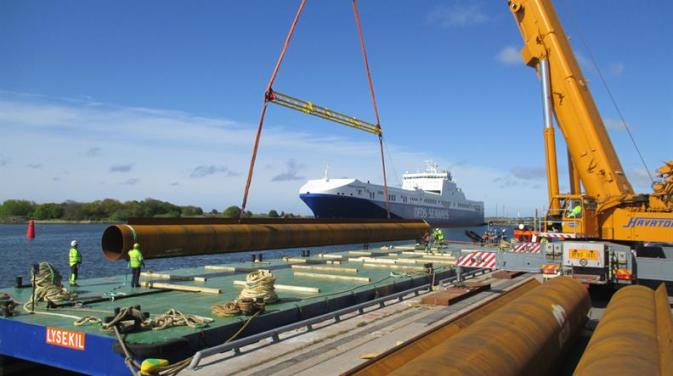 DFDS employees loading pipes on a barge with a DFDS ship in the background