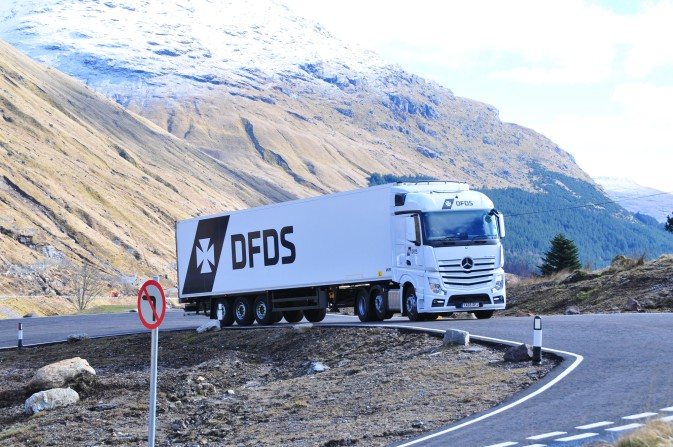 White DFDS truck climbing a mountainside highway