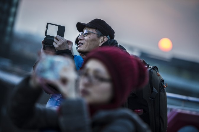 Chinese family on the deck of a DFDS vessel  taking pictures of the rising sun