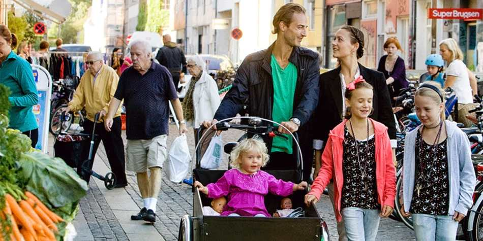 A family strolling down some cobbled, busy streets.
