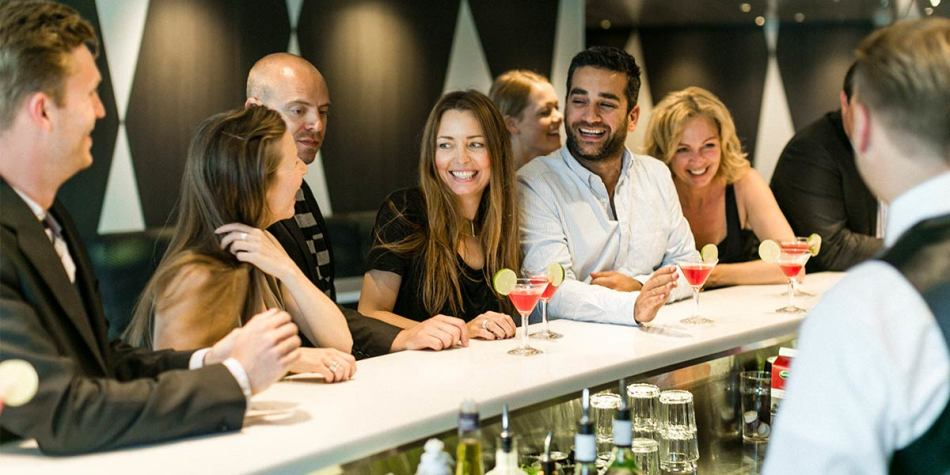 A group of friends laughing together with cocktails at a Copenhagen-Oslo cruise bar