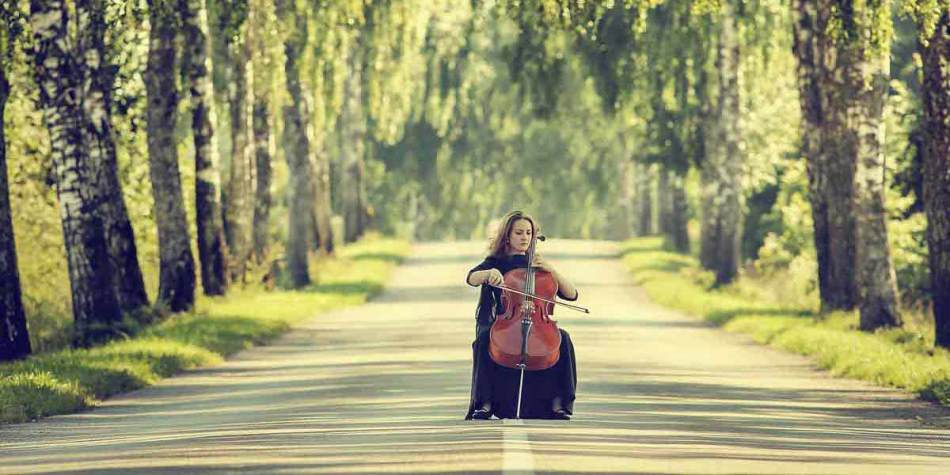 Woman playing musical instrument on a tree lined road in Central Lithuania
