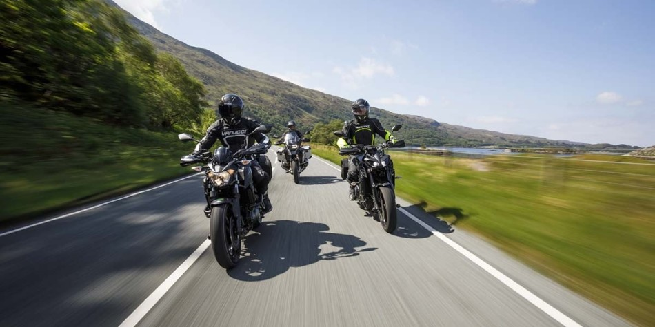 Group on motorcycles riding through landscape