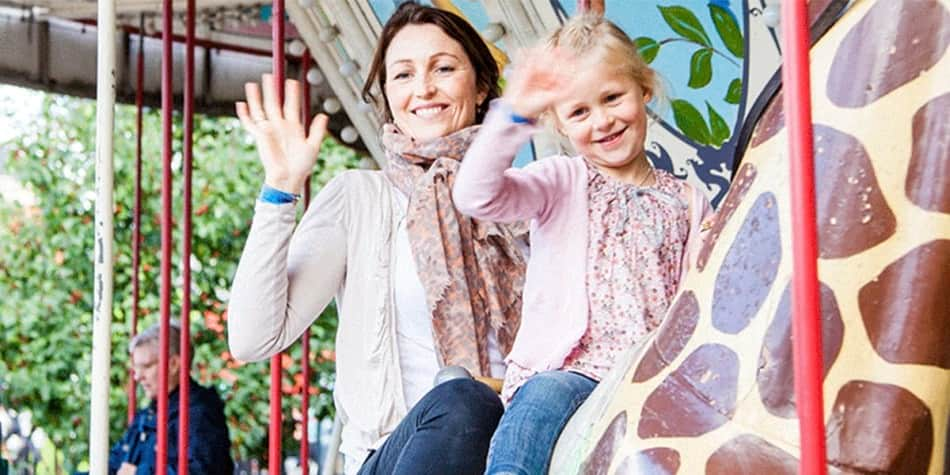 A mother and daughter on a carousel at Tivoli