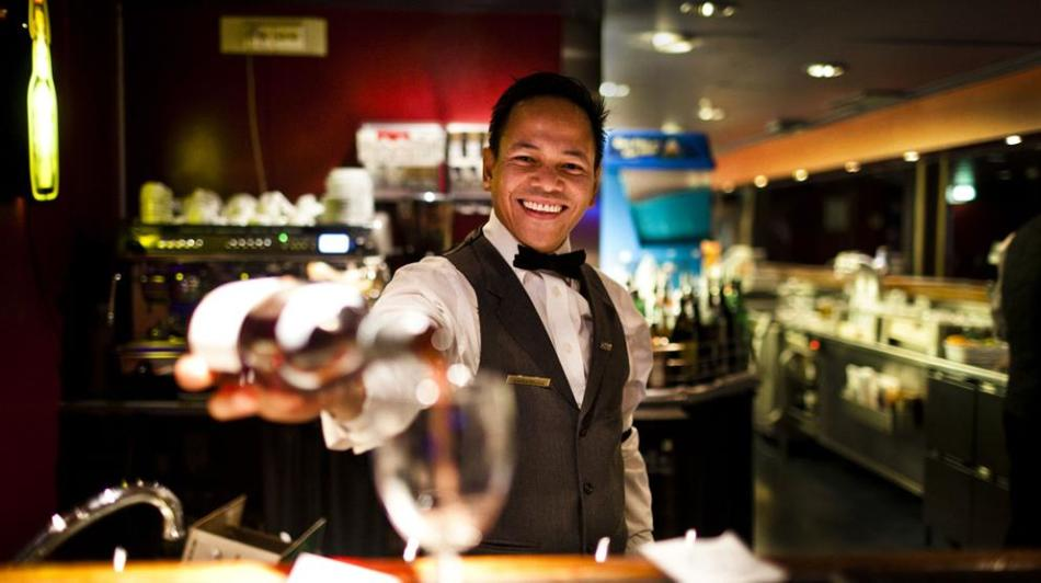 DFDS bartender pouring a glass of red wine