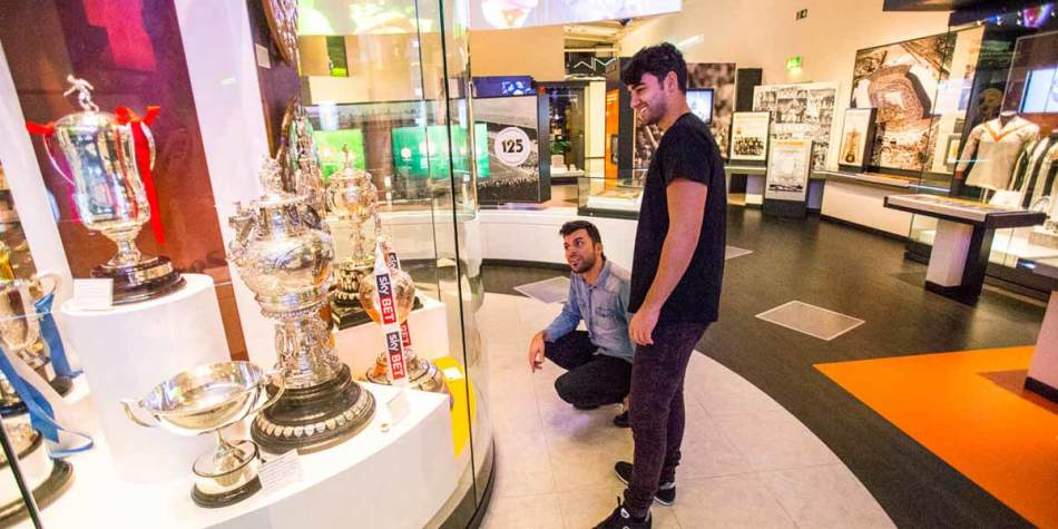 Football fans looking at museum exhibit