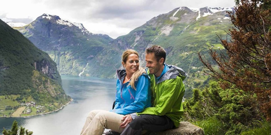 A couple sitting beside a fjord in Norway