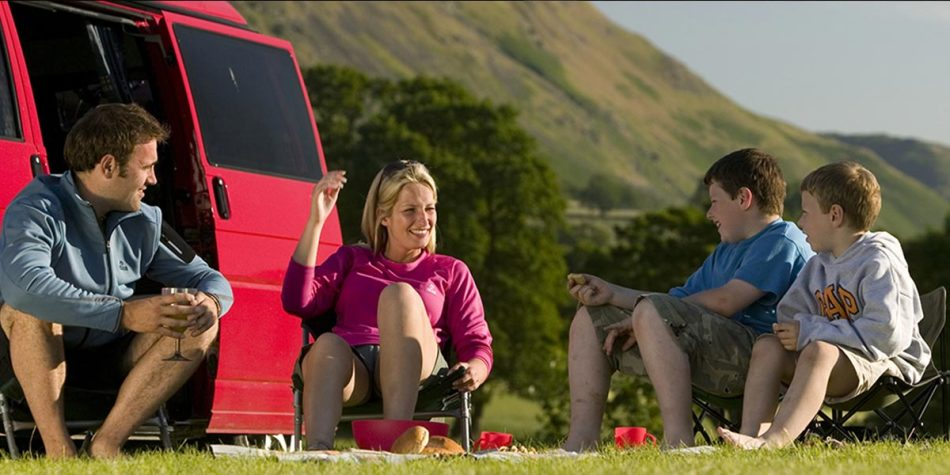 Family of four sitting on camping chairs in the Lake District