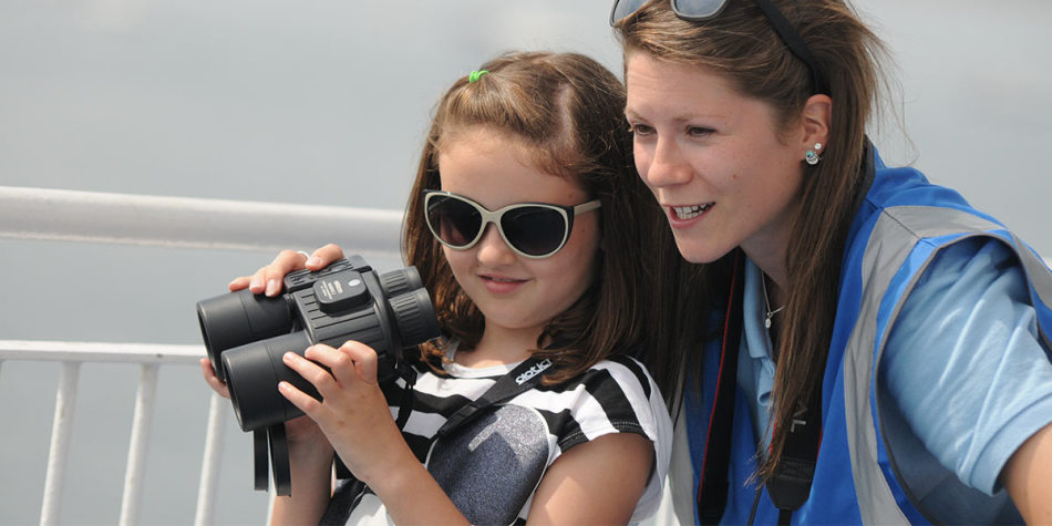 A mother and daughter using binoculars on the deck.