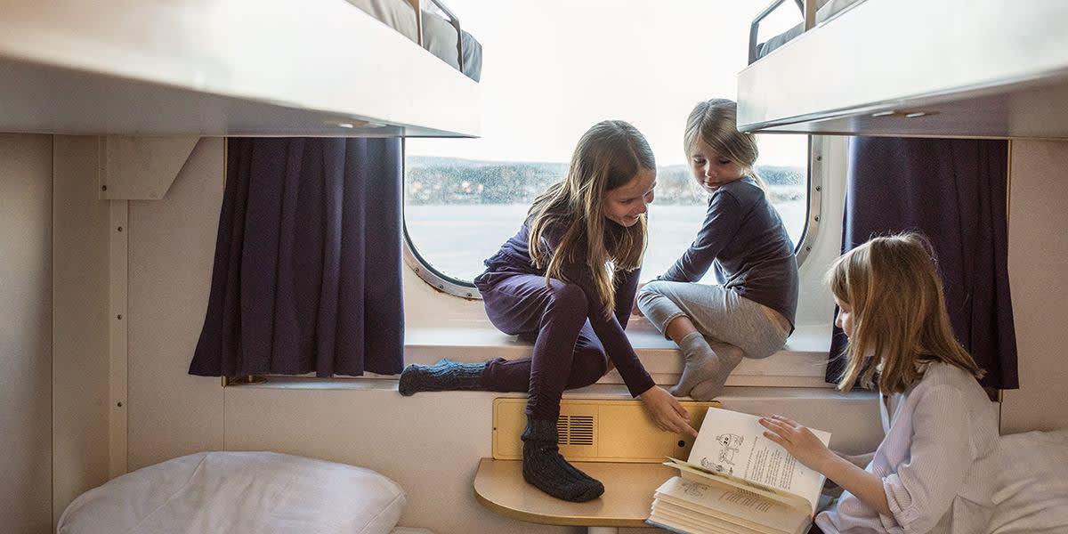 Børn hygger om bord i kahyt med vindue - familie