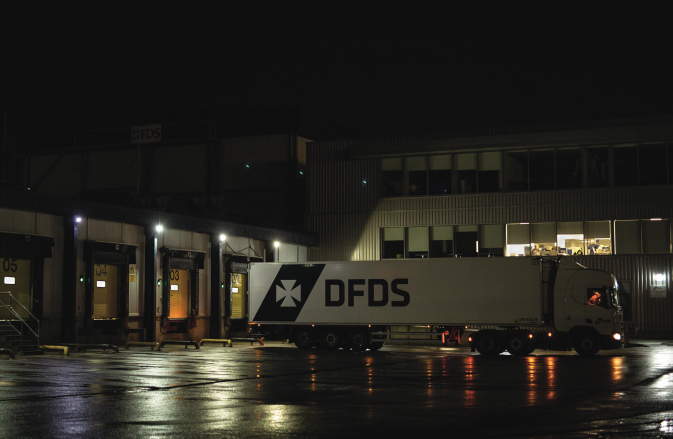 A DFDS Logistics truck leaving the terminal at night