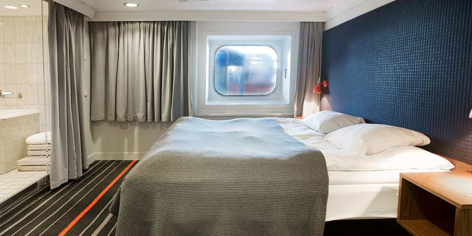 Comfortable double bed, carpeted floor and a plush looking bathroom in the commodore de luxe cabin.