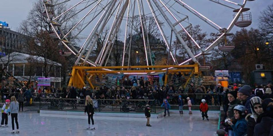 Ice rink with people skating under ferris wheel