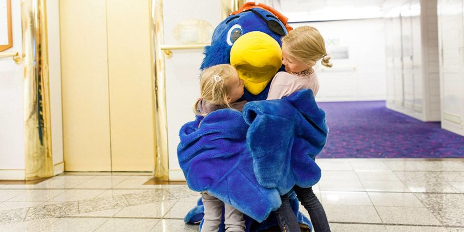 Two children being hugged by an onboard entertainer/mascot dressed up as a giant bird.