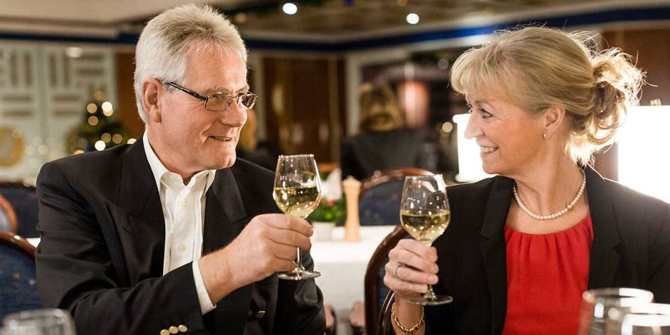 A couple drinking wine together in the onboard blue riband restaurant.