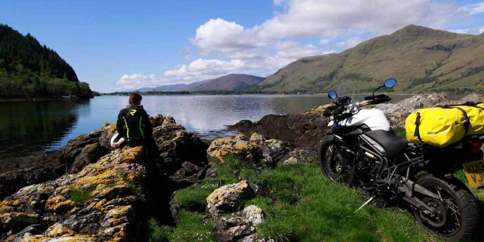 Motorcyclist sitting by lake in Scotland