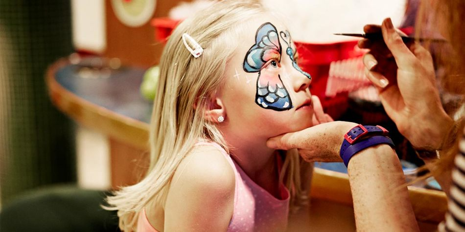 A little girl getting a butterfly painted on her face.