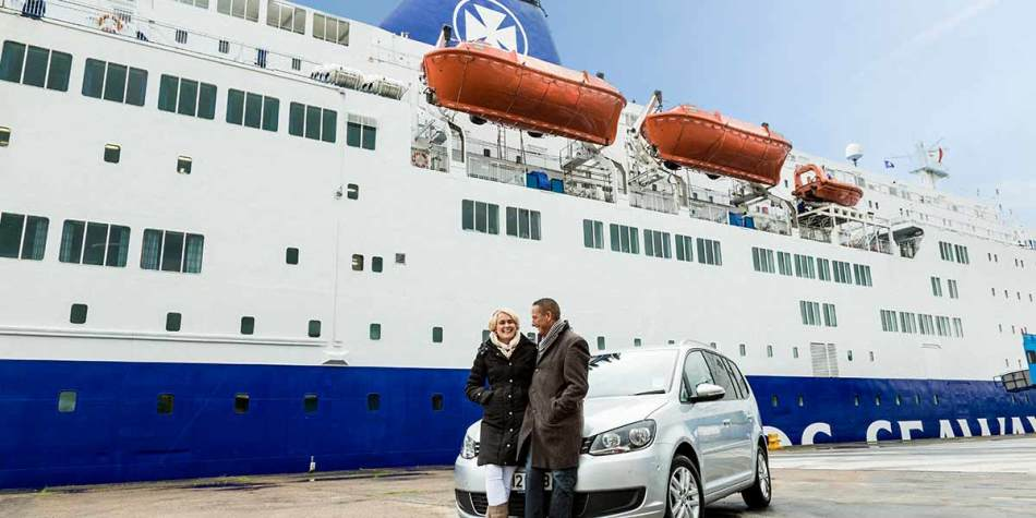 Couple outside DFDS ferry travelling with their car