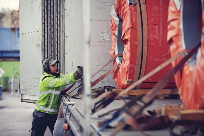 A DFDS employee loading steel coils on a DFDS Logistics truck in Gothenburg