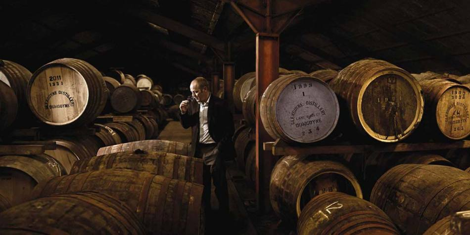 Man sipping whiskey surrounded by barrels