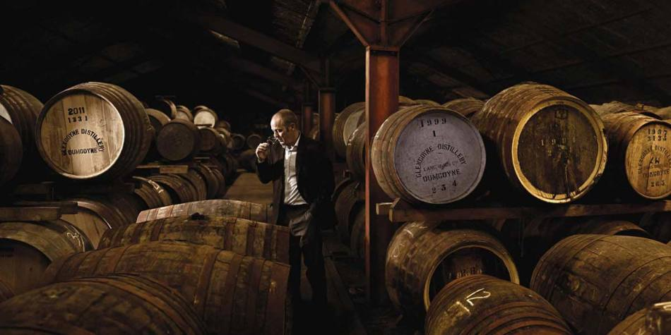 Man standing amongst whisky barrels