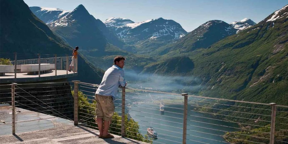 A man overlooking the nature in Norway from the comfort of a balcony.