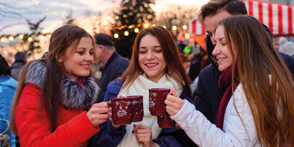 Friends drinking mulled wine at a Christmas market
