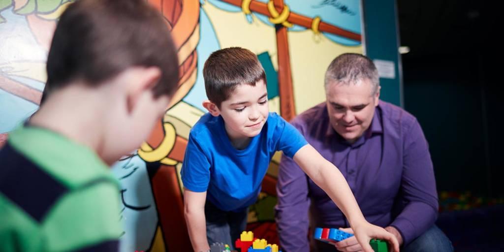 Vater spielt mit zwei Kinder im Kids club