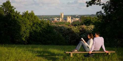 Canterbury Cathedral in the distance while a couple read on the bench